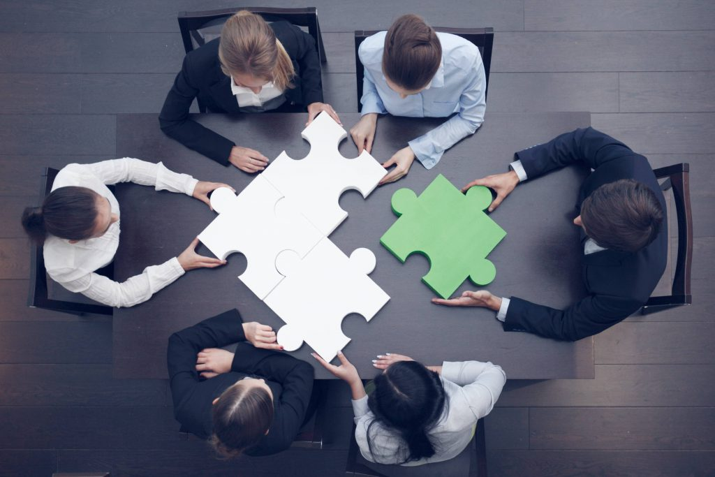 Image of colleagues putting together a puzzle illustrating JCCI grant consulting services strategic planning expertise.